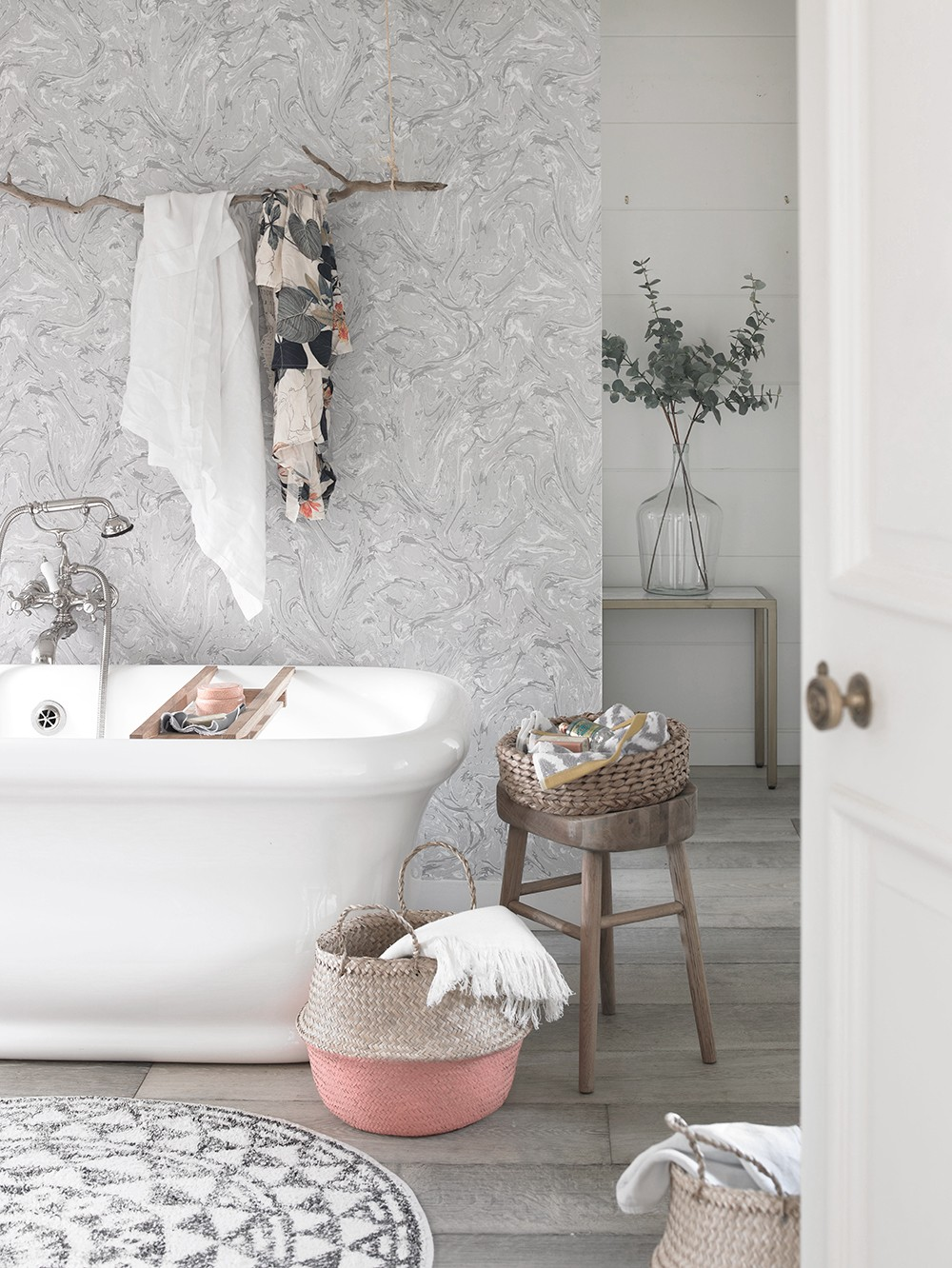 Marble effect wallpaper in the bathroom combined with soft coral accessories and a round bath mat. Shot for Country Homes & Interiors, styled by Pippa Jameson and photographed by David Britton