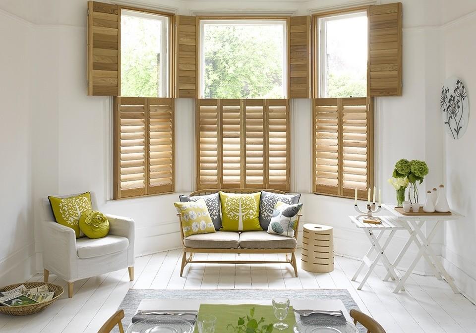 Scandinavian living room, wooden shutters, Pippa Jameson, light wood shutters, white floorboards, green and white living room