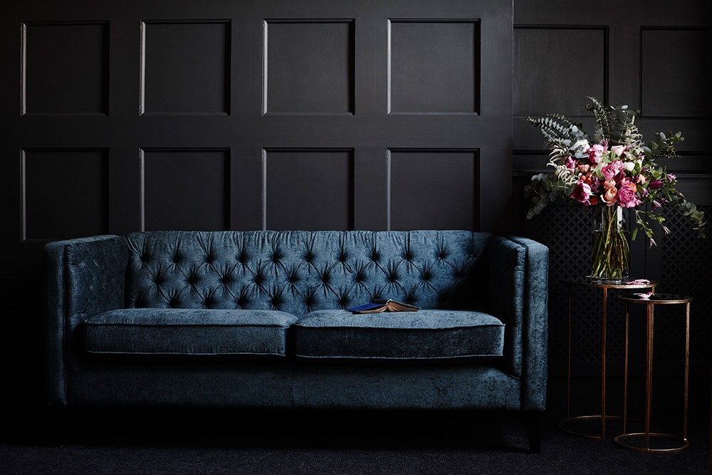 Deep velvet sofa sat against a rich grey panelled wall. Next homeware styled by Pippa Jameson and photographed by Jo Henderson.