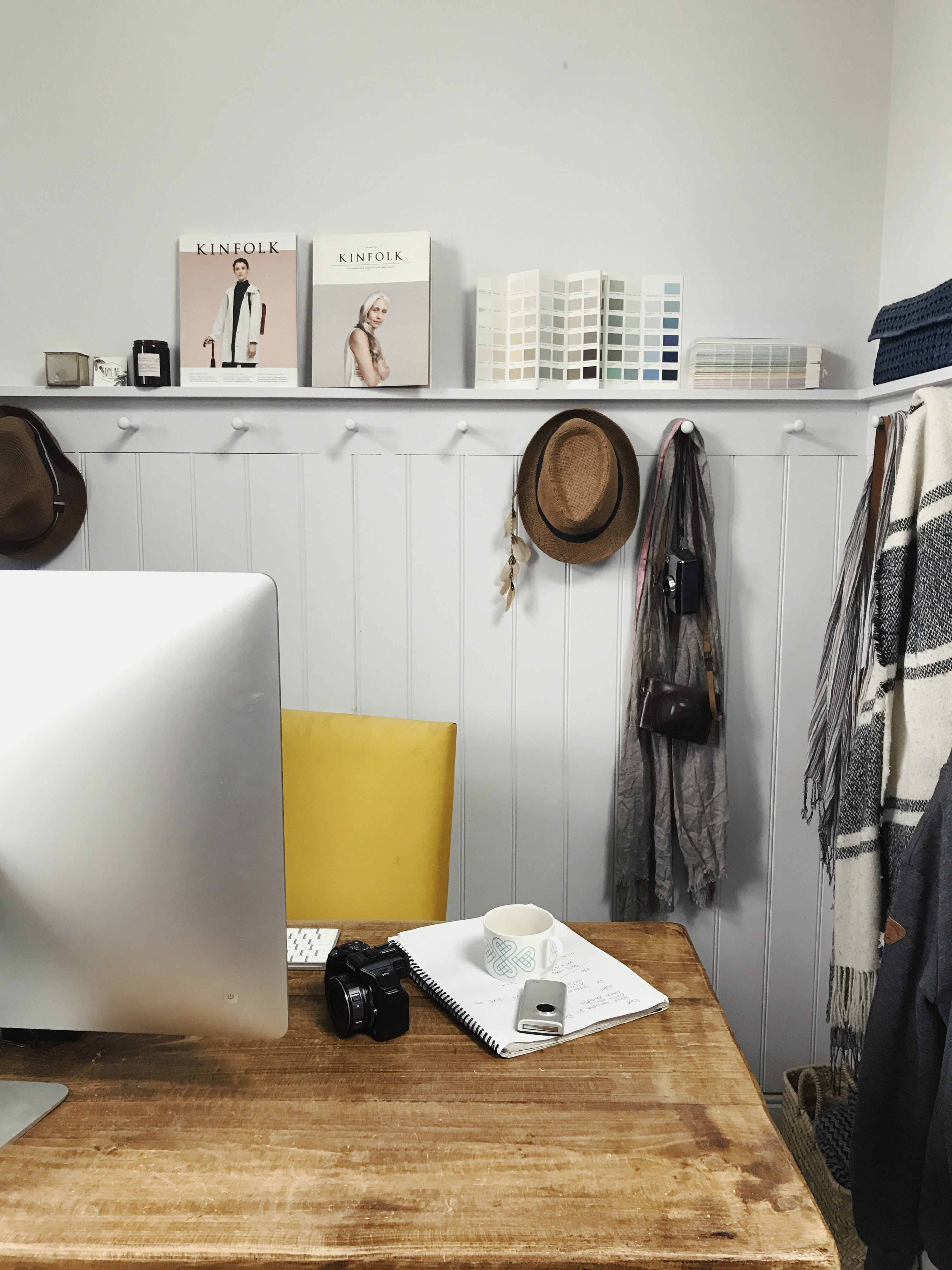 Quoting as a freelance creative: desk with computer screen and styled shelving in the background