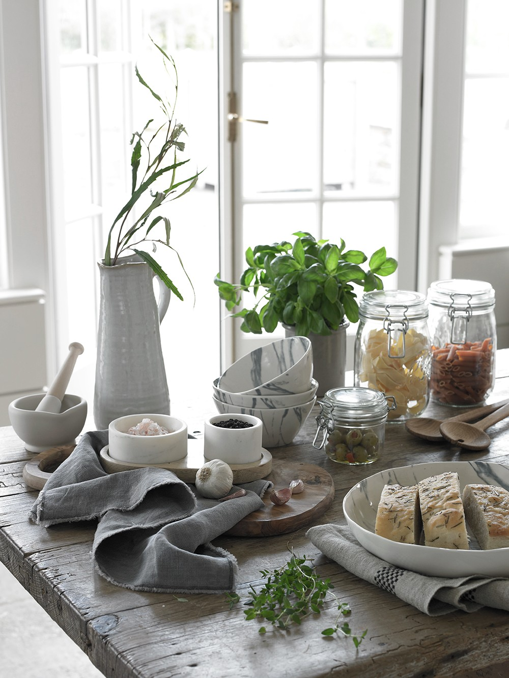 Stylish marble kitchen accessories combined with faded linen napkins, with a reclaimed wooden table. Shot for Country Homes & Interiors, styled by Pippa Jameson and photographed by David Britton