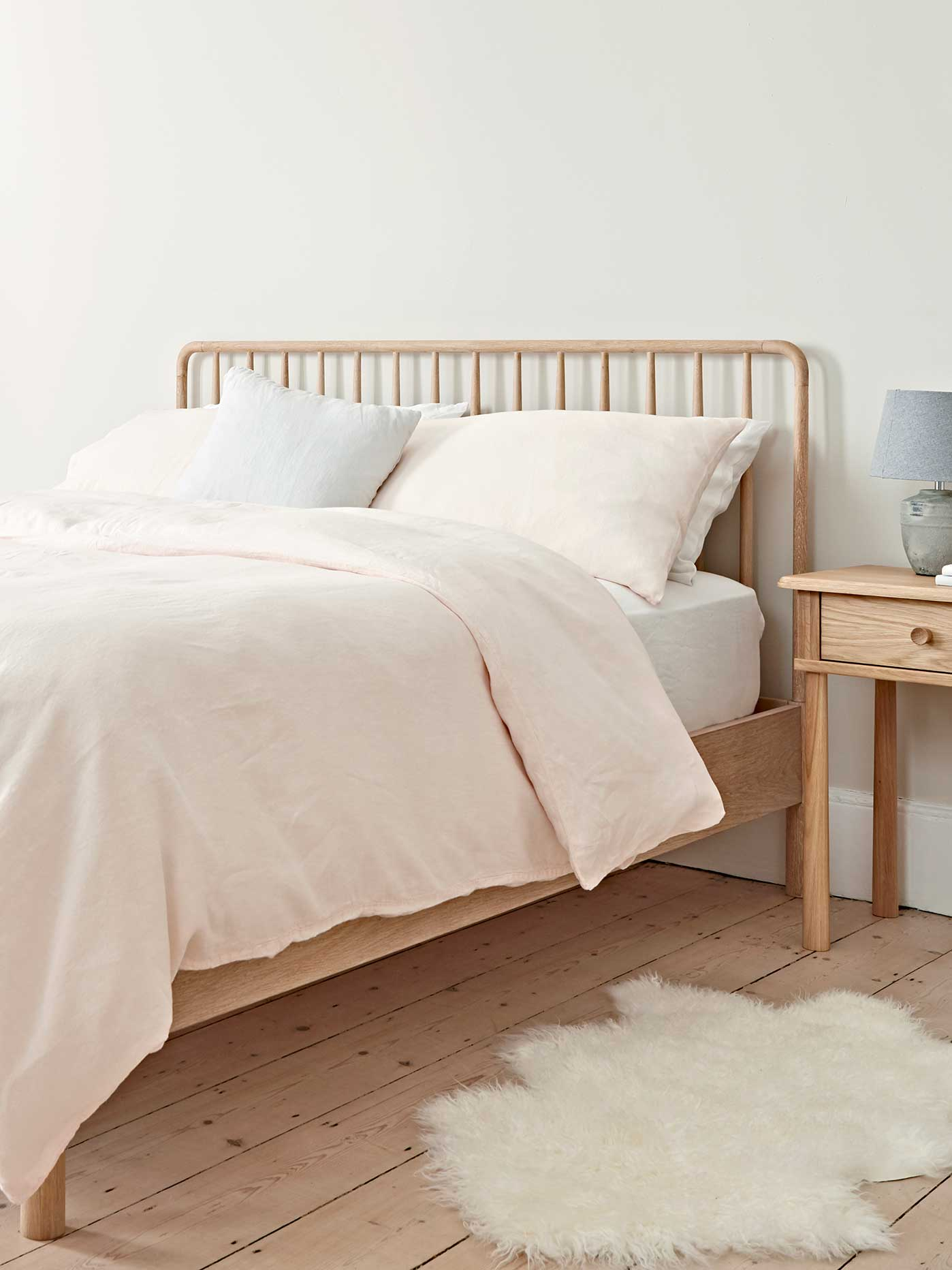 Design Storey launch: Oak bed with neutral bedding and sheepskin rug