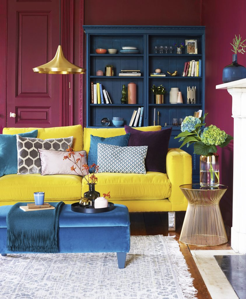 London based Interior, Pippa Jameson, shoots the cover of Good Homes magazine. Raspberry walls and a yellow velvet sofa.