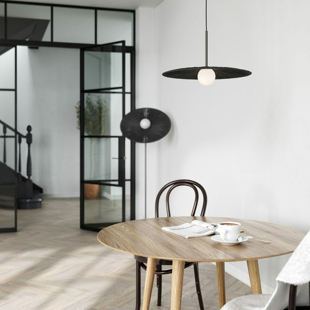 Design Storey launch: Dining table with black pendant light overhead and Crittall doors in the background