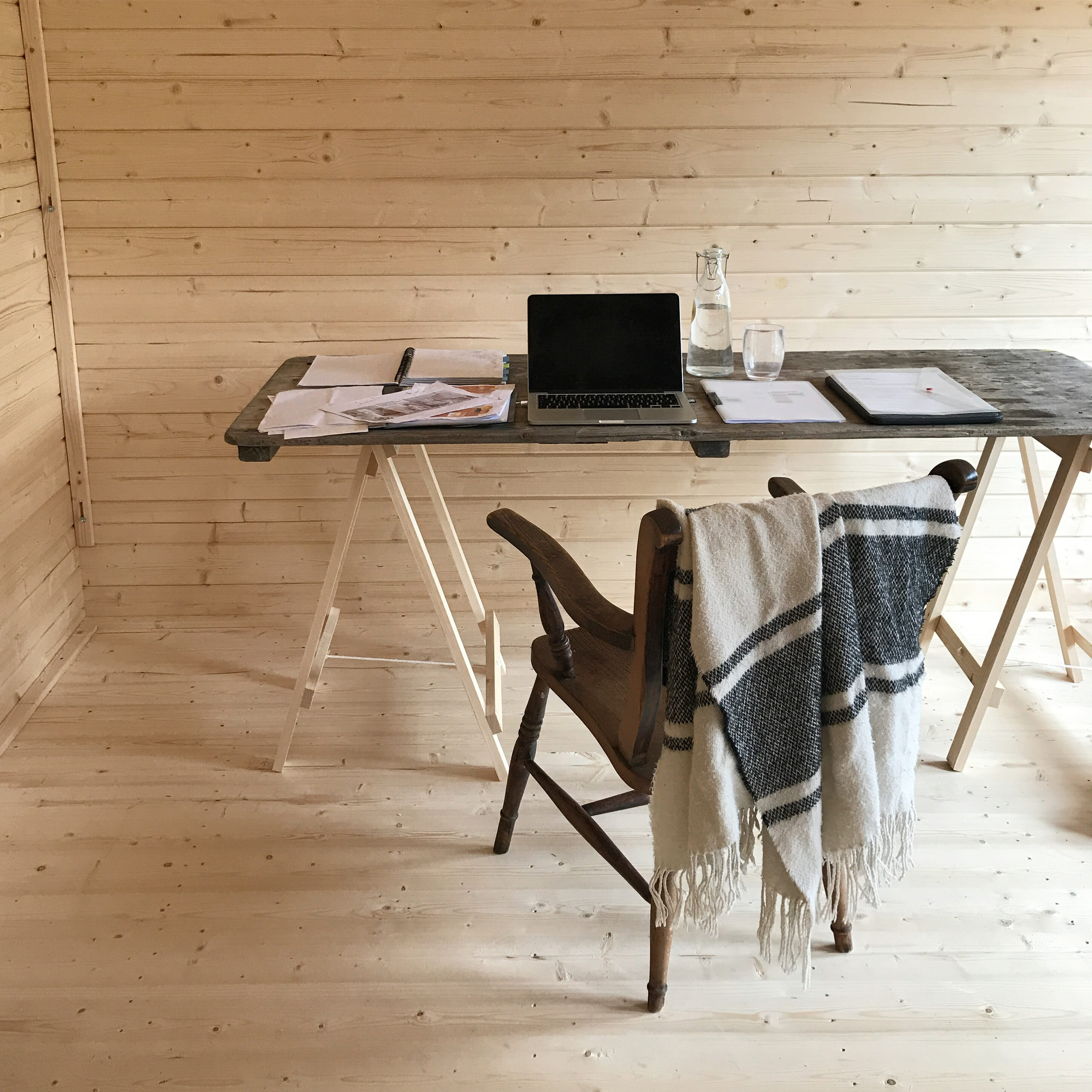 How to Make Your Business Stand Out: desk setup with open laptop, notebook and blanket draped across chair